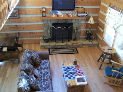 Living room: wood burning fireplace and large flat screen TV, cathedral ceiling