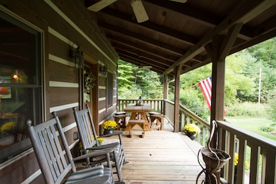 Front porch with rocking chairs and picnic table.