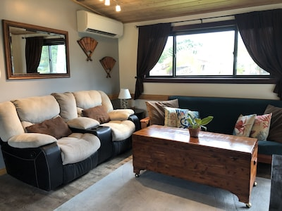 The living rooms includes a couch, a futon couch, a coffee table and tv.