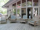 Relaxing porch with adirondacks, dining table and grill.