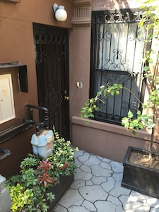 Garden apartment's private entrance with security gate.
