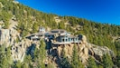 The house rests on the edge and is built into a rocky cliff.