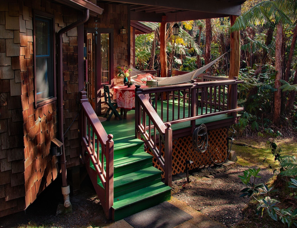 Cute Airbnb in Hawaii featuring a hammock over the green porch and located amidst a forest
