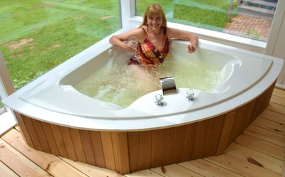 Large two person Jacuzzi in sunroom.