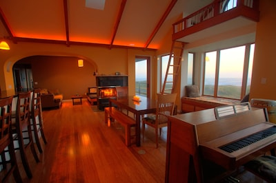 Great room w/ piano, window seat, dining table, fireplace, 180 degree ocean view