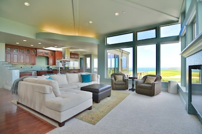 The luxurious living area with tons of natural light, ocean views and fireplac