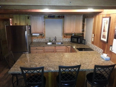 Stainless Steel, Granite Counter, Open Kitchen. Seating for 4 at counter.