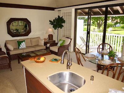 Fully remodeled open concept kitchen looks out onto private tropical gardens.