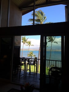 View from the living room looking out to the lanai, grounds and ocean.