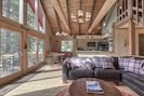 Sunny great room with floor to ceiling windows. 2 sliders exit to deck with BBQ.