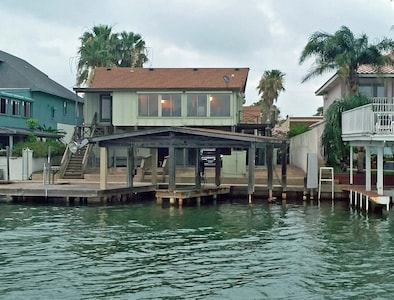 House from the water.  There's a green fishing light on the pier to night fish.