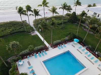 Pool with chaise, chairs, table and umbrellas.  Overlooks Gulf of Mexico.