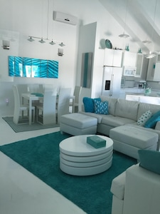 Great Room with dining area, lounge area with queen sofabeds and part of kitchen