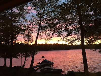 Sunset over Whalen Lake with dock and pontoon/paddle boat