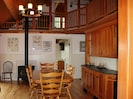 View of dining/living area with gas woodstove in the background