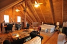 LOFT BEDROOM WITH KING SIZE BED AND DOORS LEADING TO DECK OVERLOOKING PROPERTY.