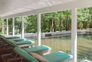 """The expansive """"floating"""" covered porch features ample lounging and dining areas."""
