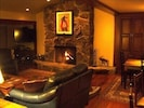 Living Room With Vaunted Ceiling, Wood Fireplace, and soft Leather Seats