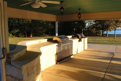 Propane grill and a smoker located in patio.  Large counter for serving.