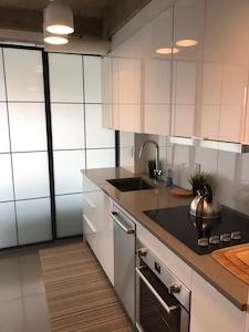 Sleek, quartz kitchen countertops and slding glass doors separates the bedroom.