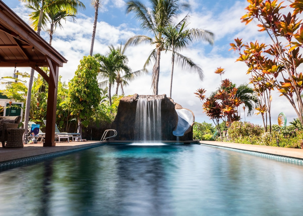 Pool with waterfall and slide in a tropical setting