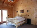 master bedroom with queen log bed and Cathedral ceilings with exposed beams
