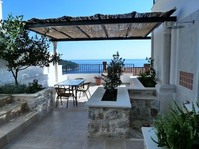 Spacious shaded terrace with sea view: ideal for outdoor dining or sunbathing.