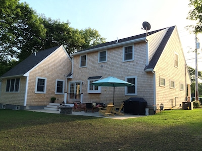 Rear view of the house with deck, patio, grill, adirondacks,two tables 12 seats.