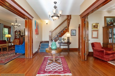 Center welcoming hall/foyer with original staircase and 3 sets of French doors.