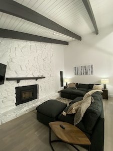 Great room w 14ft vaulted ceilings and wood fireplace overlooking the balcony.
