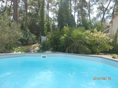 piscine hors sol sur terrasse avec vue sur jardin et forêt