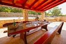 Großer Esstisch auf der Außenterrasse mit Holzkohlegrill