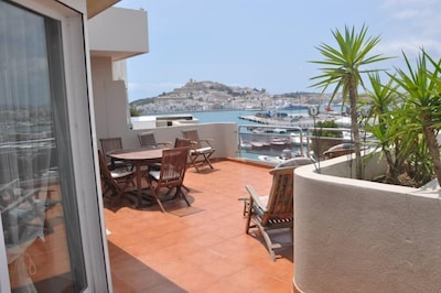 Very large terrace, dining table and sun beds, view to the pool and Dalt villa