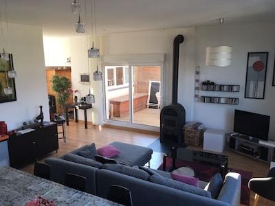 Vue du salon séjour avec accès à la terrasse prise depuis le coin cuisine
