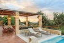 Outdoor dining and lounging areas under the shade of a pergola