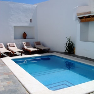 Private swimming pool with four sun loungers and a covered area for BBQs