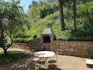 Barbecue réalisé en pierres sèches du pays et adossé à la terrasse.