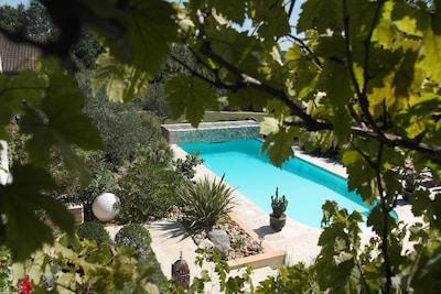 La piscine chauffée du 15 avril au 15 octobre dans son environnement de verdure