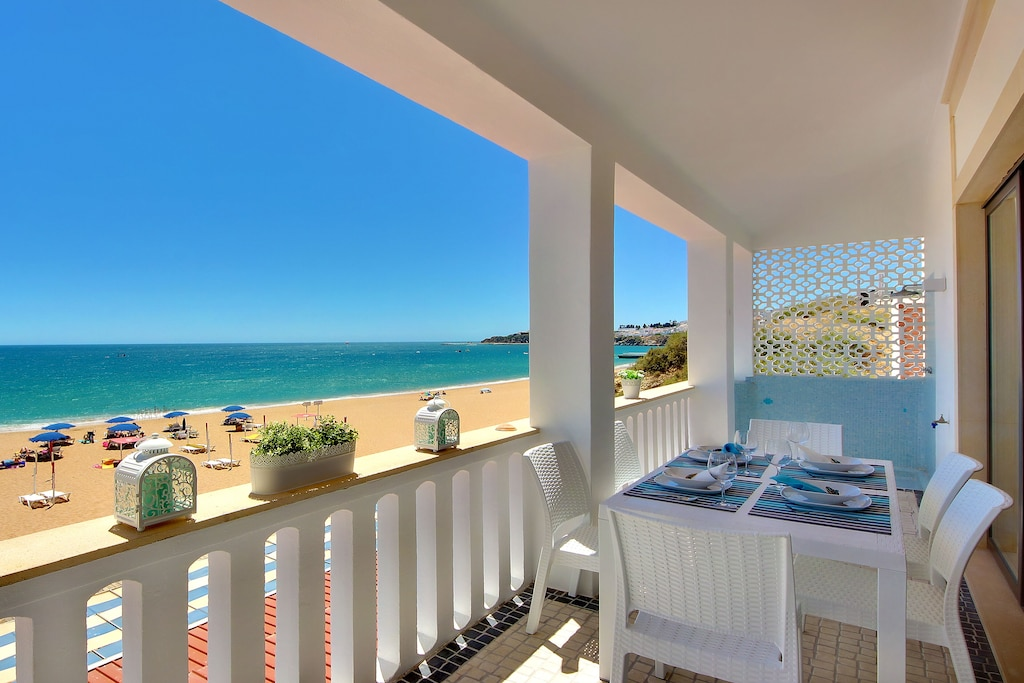 Terrace with white furniture overlooking one of the top beaches in Portugal