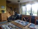Wohnzimmer mit Gartenblick, Kaminofen und Treppe in das Obergeschoss.