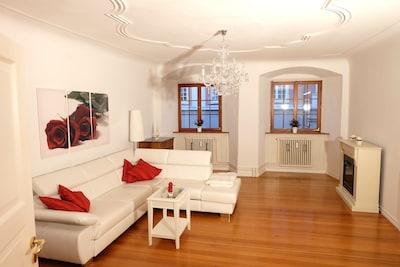 Blick ins helle barocke Wohnzimmer mit Stuckdecke, Kronleuchter und Ledercouch