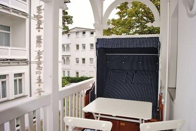 Balkon in alter bäderarchitektur mit Strandkorb und Sitzgruppe