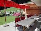 Terrasse mit Tischen, Liegen, Schirmen und Überdachung