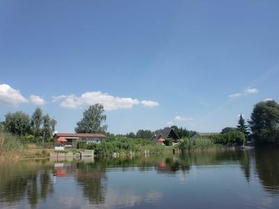 Ansicht vom Angel- und Badesee auf die drei Ferienhäuser