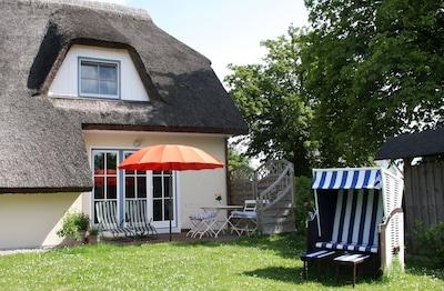 Gartenansicht des Ferienhauses mit Sonnen-Terrasse, Liegestühlen und Strandkorb