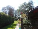 Blick vom Gartentor in den sommerlichen Garten.