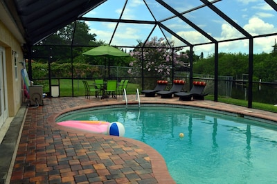 Pool area , with tables, chairs and pool loungers.Nice screened area to hang out