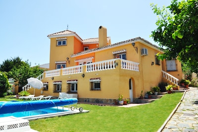 Front of the villa showing part of garden and pool - has cover and safety fence