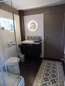 Salle de bain avec douche, radiateur porte-serviettes
