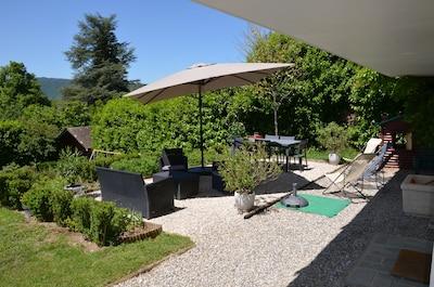 Terrasse avec salon de jardin, transat et un coté salle à manger